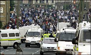 Hundreds of youths gather in front of a line of police vans