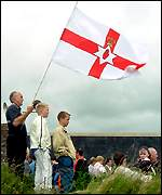 A man and his children raise a loyalist flag on Drumcree Hill