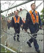 Marchers pass St John's Church surrounded by razor wire