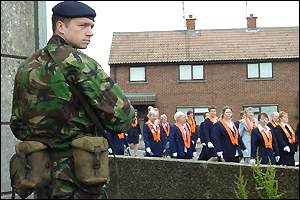 A soldier stands in front of nationalist housing as the Drumcree parade passes