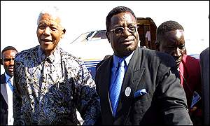 Nelson Mandela (left) is accompanied by an aid as he arrives at Lusaka International Airport for the 37th OAU heads of states summit