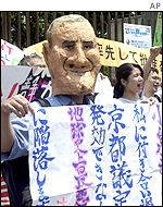 A Japanese protester in George Bush mask flashes a banner urging the government to ratify the Kyoto treaty.