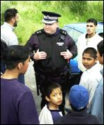 Policeman talking to Asian youths
