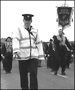 A solitary policeman escorts the parade