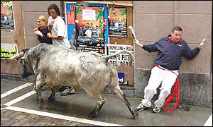 Onlookers flatten themselves against the wall as a bull runs past