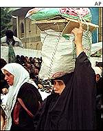 Iraqi woman carrying food rations