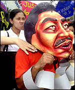 An anti-Estrada demonstrator directs her anger at an actor wearing a caricature of Estrada with his hands tied