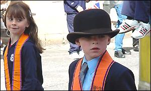 A boy and a girl in orange regalia take part in a march