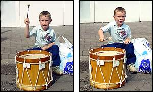 A child bangs a drum along the route of a parade in Belfast