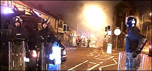 Police officers in full riot gear man a blockade in Burnley on 24 June 2001