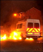 Police vehicles drive through flames in Oldham on May 28 2001