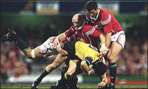 Stephen Larkham is tackled by Keith Wood and Martin Johnson