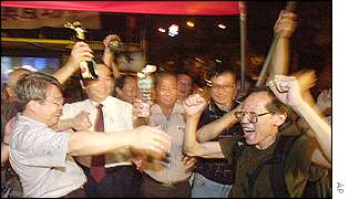 Supporters of Taiwan's pro-China New Party break celebrate after watching the announcement on a live television broadcast