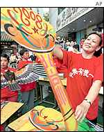 A Beijing woman shows a kite with an Olympic design