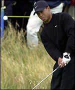 Tiger Woods chips onto the third green