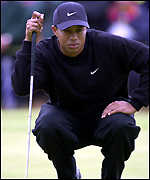 Tiger Woods lines up a putt on the fourth green