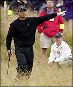 Tiger Woods gestures at the ball after playing from the rough at the sixth