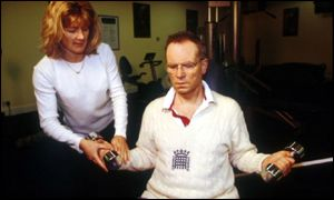 Archer clad in jumper, with weights and unidentified female trainer