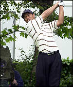 Tiger Woods tees off at the first hole in round two