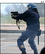 Policeman firing tear gas