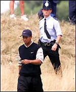 Tiger Woods walks in the rough, with a police escort