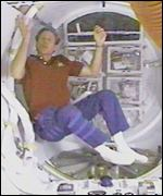 Astronaut floating in capsule