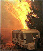 [ image: Flames burn trees around a caravan]