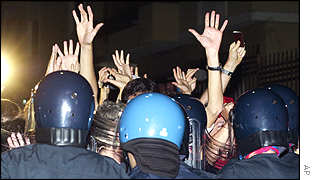 Protesters raise their hands in surrender as the police raid their centre