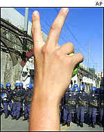 Protester making a V sign as police advance
