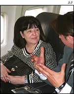 Mira Markovic talks to an aide on the flight to the Netherlands