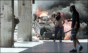hooded protesters in front of burning car