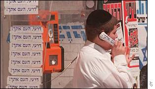 Israeli man in phone booth covered with election stickers for the Shas religious party