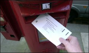 Person putting postal ballot into post box