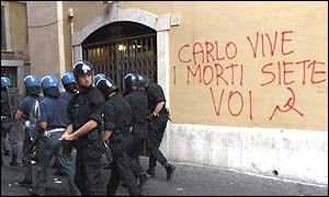 Riot police walk past a wall bearing graffiti referring to young protestor Carlo Giuliani who was shot dead during the protests