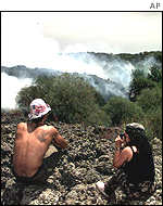 Tourists watching smoke rising from the slopes of Mount Etna