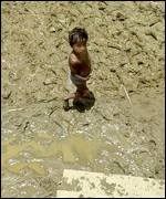 Boy in mud of lake