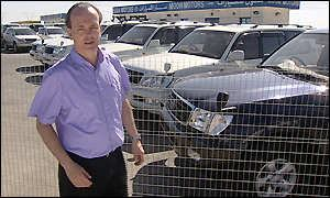 Quentin Willson stands in front of stolen Japanese cars all intended for sale in the UK