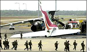 A Sri Lanka Airlines plane lies in ashes on the tarmac of the international airport as troops march by