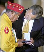 George W. Bush giving a medal to one of the Navajos