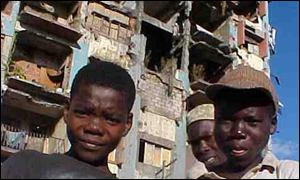 Children next to a ruined block of flats in Angola