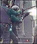An RUC officer fires a plastic baton round in a riot situation in Northern Ireland