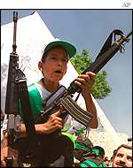 Boy brandishing a gun at a Palestinian funeral