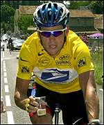 Lance Armstrong has a swig of champagne on the road to Paris