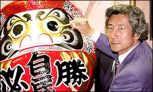 Prime Minister Junichiro Koizumi paints eyes on a Dharma doll, a mascot of victory