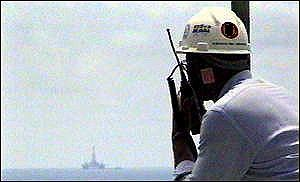 Angolan oil worker looks out at deepwater drilling rig