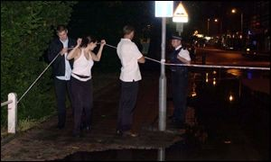 Three people try to get under the police cordon