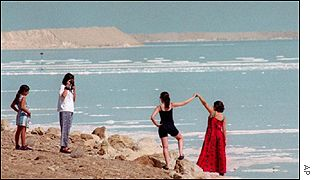 Israeli tourists pose for a photo on the shore of the Dead Sea