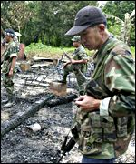 Soldiers inspect the remains of a building burned by the Abu Sayyaf