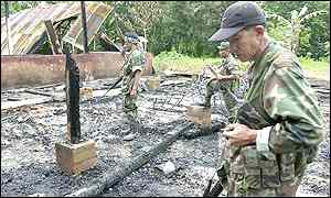 Militiamen inspect a school building razed by the Abu Sayyaf in the town of Lamitan