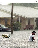 A man wades through floodwater in Florida on 2 August